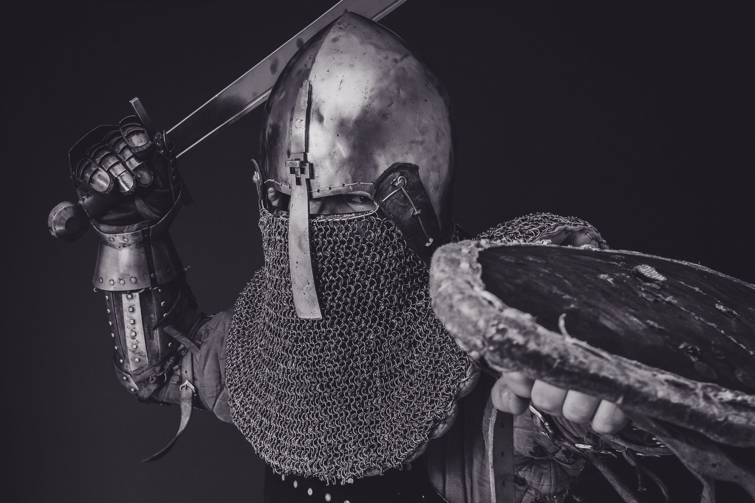 Man in armor stands poised with sword and shield